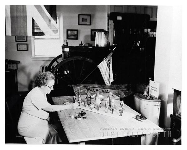 'WACHOVIA MUSEUM / 1939 / MRS. MABEL WOLF / REPAIRING ESKIMO DOLLS.'