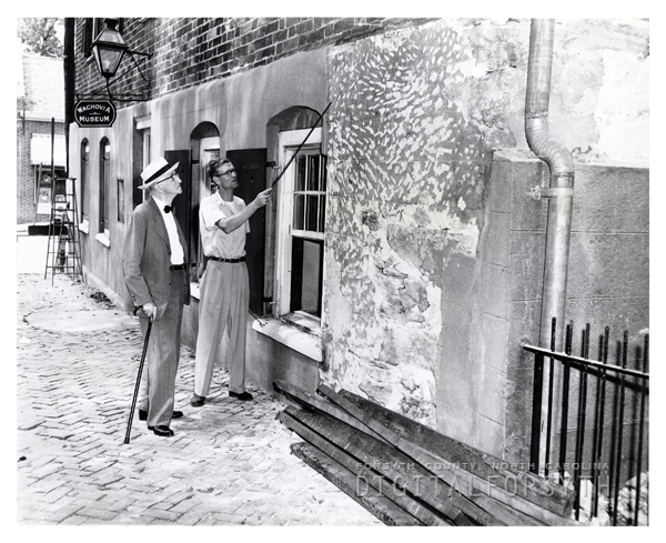 'John Griffin pointing out original plaster to Mr. B. J. Pfohl / Wachovia Museum'