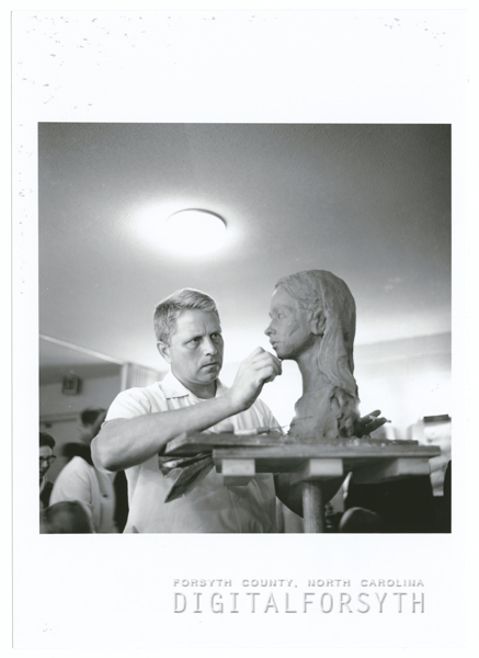 Man sculpting in clay at the Arts Council office at the James G. Hanes Community Center, 1964.