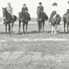 Horses and riders at a racetrack.
