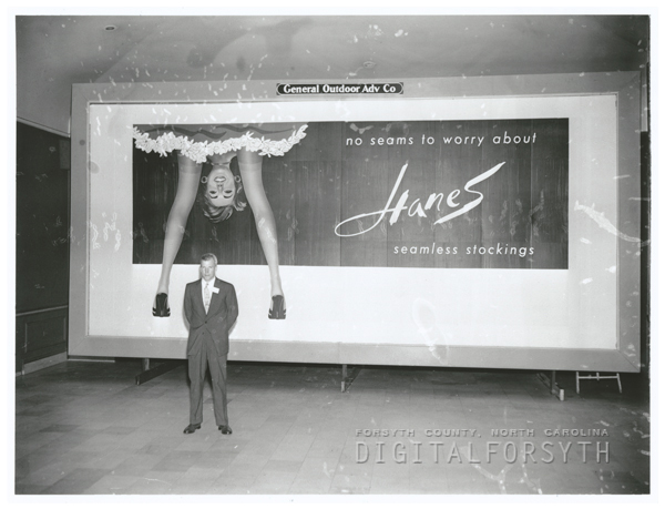 Gordon Hanes, of Hanes Corporation, in front of a Hanes Hosiery billboard, 1956.
