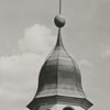Steeple, flag, and clock on top of Home Moravian Church.