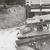Heavy rain causes damage to dam spillway in the Janita Lakes area, releasing a flood across Ebert Street, 1959.
