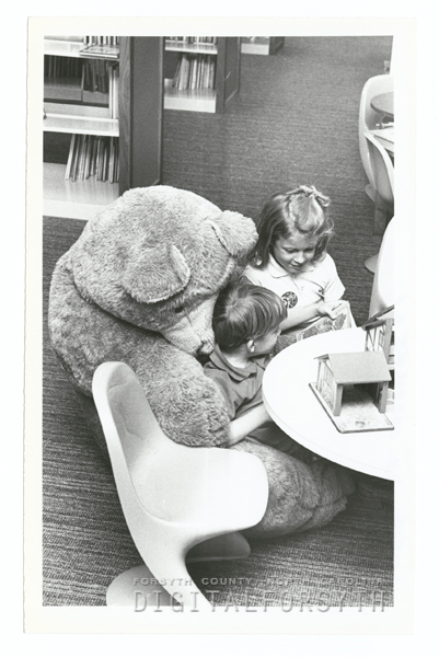 Children looking at books, one child getting a bear hug.