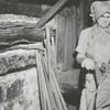 Woman stringing tobacco leaves at a tobacco barn, 1955.