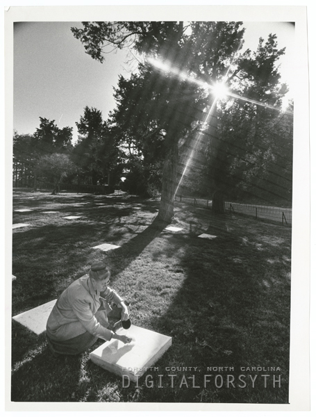 Mrs. Edward Shouse cleaning a gravestone in the Kernersville Moravian Church graveyard, 1970.