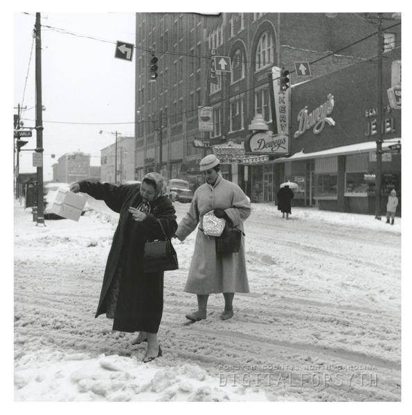 Women crossing W. Fourth Street near Trade Street in the snow, 1960.