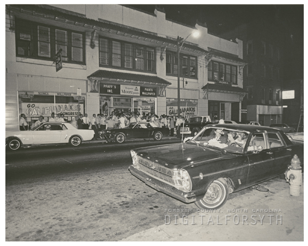 Smith Bagley in his car at right in front of the Galifianakis campaign headquarters, 1966.