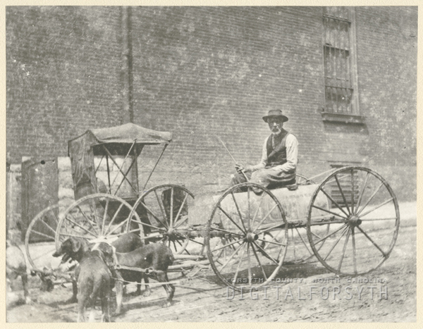 Unidentified man in a wagon near a buggy.
