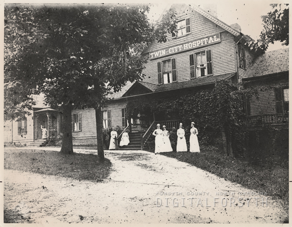 Nurses standing in front of the Twin City Hospital on Brookstown Avenue.